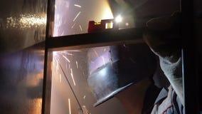 El trabajador del soldador realiza la soldadura del salto El soldador del trabajador realiza el proceso de la soldadura por arco  almacen de metraje de vídeo