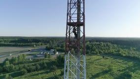 El trabajador del técnico que mantenía al hombre celular de la antena se vistió en uniforme y el casco sube las escaleras en trab