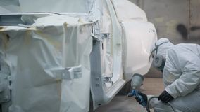 El trabajador del taller de la pintura en un garaje está utilizando un arma de espray para cubrir la superficie de la carrocería  almacen de metraje de vídeo