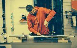 El trabajador del taller de reparaciones del esquí ajusta los atascamientos Fotografía de archivo libre de regalías