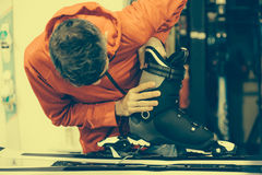 El trabajador del taller de reparaciones del esquí ajusta los atascamientos Imagenes de archivo