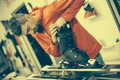 El trabajador del taller de reparaciones del esquí ajusta los atascamientos Imagen de archivo libre de regalías