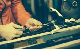El trabajador del taller de reparaciones del esquí ajusta los atascamientos Fotos de archivo