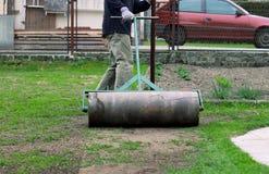 El trabajador del verano tira del rodillo del césped para aplana el jardín Pesado, el cilindro del hierro pisotea el suelo y el h fotografía de archivo