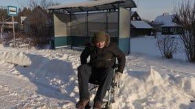 El trabajador discapacitado en la silla de ruedas cuenta con el autobús almacen de metraje de vídeo