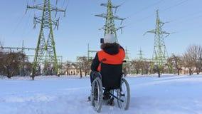 El trabajador discapacitado en la silla de ruedas lleva imágenes cerca las líneas de alto voltaje almacen de video