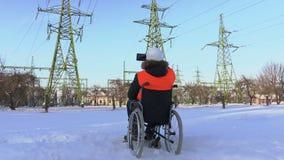 El trabajador discapacitado lleva imágenes cerca las líneas de alto voltaje almacen de video
