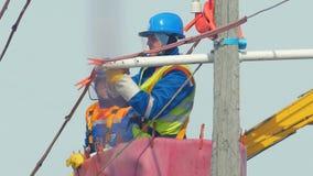 El trabajador en casco conecta el cable en polo en cuna de la grúa del camión almacen de video