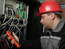 El trabajador en casco rojo hace medidas eléctricas Fotografía de archivo