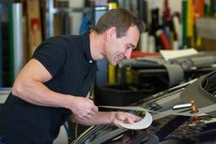 El trabajador en el coche que envuelve el taller pega la hoja al coche Foto de archivo libre de regalías