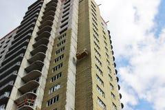 el trabajador en frente amarillo suspendió la cuna en un edificio alto nuevamente construido fotografía de archivo