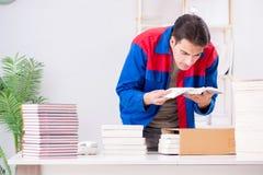 El trabajador en la casa editorial que prepara orden del libro fotografía de archivo