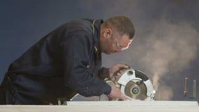 El trabajador en la fábrica regula un pedazo de lado de la mosca de madera y del serrín a cámara lenta metrajes