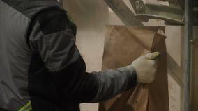 El trabajador en máscara toma la bolsa de papel con la mezcla constructiva seca almacen de metraje de vídeo