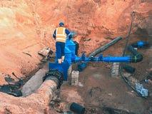 El trabajador en ropa de la seguridad conduce el conducto de la válvula en el tubo de agua potable de la ciudad fotografía de archivo