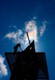 El trabajador en shilouttee repara la torre Fotografía de archivo