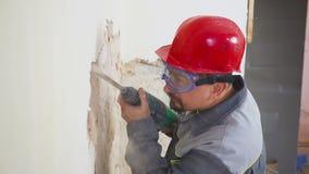 El trabajador en traje protector demuele la pared del yeso E Equipo protector personal r almacen de metraje de vídeo