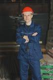 El trabajador en un casquillo y un uniforme rojos se opone al contexto de t fotos de archivo libres de regalías