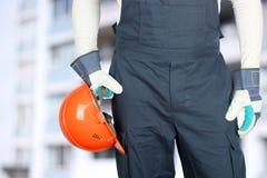 El trabajador en un emplazamiento de la obra sostiene un casco Foto de archivo