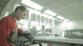 El trabajador en uniforme pule piezas del coche de metal con la herramienta especial almacen de metraje de vídeo