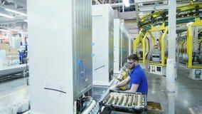 El trabajador en vidrios conecta los tubos con los lados de los refrigeradores detrás metrajes