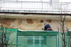 El trabajador en vidrios protectores y un respirador procesa la pared con una amoladora de ángulo antes de la restauración y de e Imagen de archivo