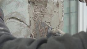 El trabajador enyesa la pieza de la pared verde con la herramienta de la espátula en área de la construcción almacen de metraje de vídeo