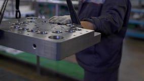 El trabajador es detalle de metales pesados grande de levantamiento al lado de las cuerdas en un taller y la eliminación de él so almacen de video