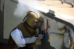 El trabajador es quita la pintura arruinando de arena de la presión de aire Imágenes de archivo libres de regalías