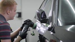 El trabajador está creando un revestimiento protector en el tinte del automóvil, frotamiento haciendo girar la máquina de pulir e almacen de video