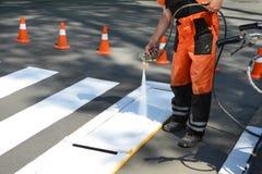 El trabajador está pintando un paso de peatones peatonal El trabajador técnico del hombre del camino que pinta y que comenta el p Fotos de archivo libres de regalías