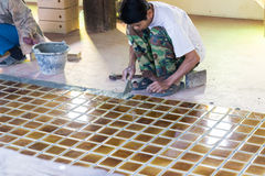 El trabajador está poniendo la teja marrón en el piso imágenes de archivo libres de regalías