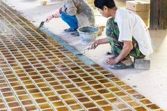 El trabajador está poniendo la teja marrón en el piso foto de archivo libre de regalías