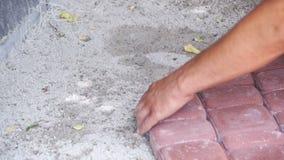 El trabajador está poniendo piedras de pavimentación usando el martillo Cámara lenta almacen de video