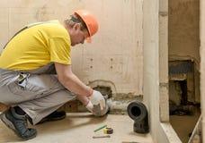 El trabajador est? poniendo un tubo de desag?e de las aguas residuales foto de archivo