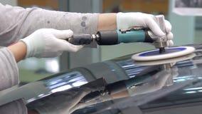 El trabajador está puliendo la capilla del automóvil por la máquina de pulir almacen de video