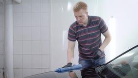 El trabajador está puliendo la capilla negra del coche en un auto-servicio, frotando por el trapo suave después de lavar a la car almacen de video