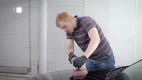 El trabajador está puliendo la capilla negra del coche en un auto-servicio, frotando por el trapo suave después de lavar a la car metrajes