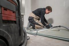El trabajador está utilizando una herramienta constructiva, las herramientas que muelen y un aspirador mampostería seca en novent foto de archivo