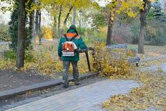 El trabajador está limpiando las hojas caidas con el ventilador de la mochila Foto de archivo libre de regalías