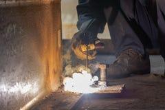 El trabajador fabrica la estructura por proceso de la soldadura al arco de metal del escudo Imagenes de archivo