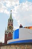 El trabajador fija una bandera del día de fiesta en la Plaza Roja adentro Foto de archivo