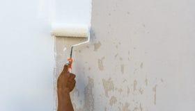 El trabajador gasta la pintura del rodillo en pared Foto de archivo