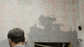 El trabajador hace la enyesado del trabajo en un muro de cemento, trabajando con una paleta metrajes
