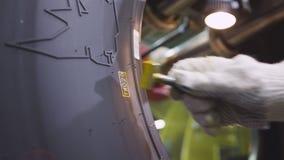 El trabajador hace la marca del número en Lorry Tire Side Closeup metrajes