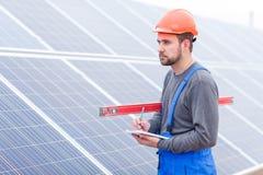 El trabajador hace notas en un cuaderno y anticipa contra un fondo de los paneles solares Imagen de archivo