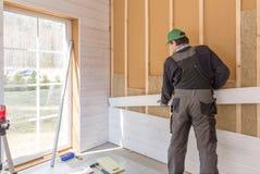 El trabajador hace trabajos del acabamiento de paredes con un tablero de madera blanco, usando nivel de línea del laser Construcc Imagen de archivo