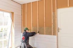 El trabajador hace trabajos del acabamiento de paredes con un tablero de madera blanco, usando nivel de línea del laser Construcc Fotografía de archivo libre de regalías