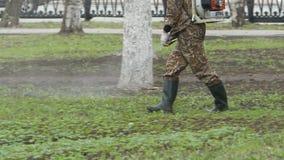 el Trabajador-hombre procesa un parque contra ácaro y parásitos de cosecha Tratamiento sanitario del parque almacen de metraje de vídeo