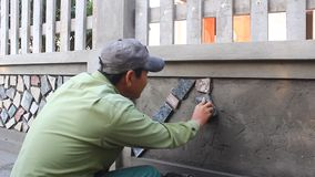 El trabajador instala la superficie de la pared de piedra con el cemento metrajes